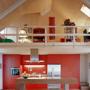 Offene, Einzeilige, Große Moderne Küche mit flächenbündigen Schrankfronten, Arbeitsplatte aus Holz, Küchenrückwand in Orange, Küchengeräten aus Edelstahl, braunem Holzboden, Kücheninsel und roten Schränken in München