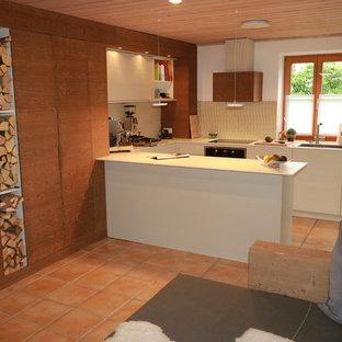 ミュンヘンの中サイズのカントリー風おしゃれなキッチン (フラットパネル扉のキャビネット、白いキャビネット、人工大理石カウンター、一体型シンク、ベージュキッチンパネル、トラバーチンの床、シルバーの調理設備の、テラコッタタイルの床、赤い床) の写真