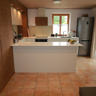 Design ideas for a mid-sized country u-shaped open plan kitchen in Munich with an integrated sink, flat-panel cabinets, white cabinets, solid surface benchtops, beige splashback, travertine splashback, stainless steel appliances, terra-cotta floors, a peninsula and red floor.