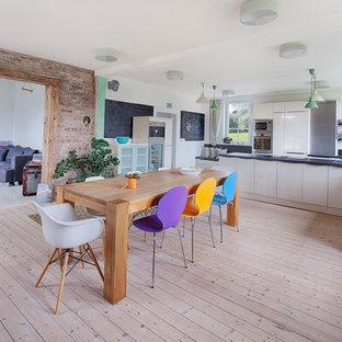 Modelo de cocina comedor en L, contemporánea, grande, con fregadero sobremueble, armarios con paneles lisos, puertas de armario beige, electrodomésticos de acero inoxidable, suelo de madera clara y península