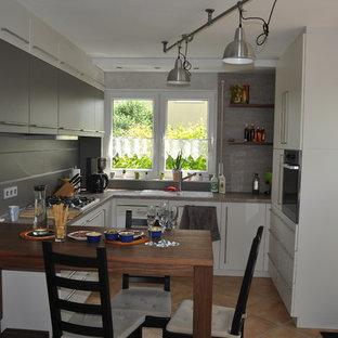 ブレーメンの小さいコンテンポラリースタイルのおしゃれなキッチン (一体型シンク、フラットパネル扉のキャビネット、白いキャビネット、人工大理石カウンター、マルチカラーのキッチンパネル、ガラス板のキッチンパネル、カラー調理設備、テラコッタタイルの床、赤い床、マルチカラーのキッチンカウンター) の写真