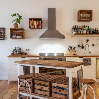 Example of a trendy single-wall medium tone wood floor and brown floor kitchen design in Berlin with a drop-in sink, flat-panel cabinets, white cabinets, wood countertops, white backsplash, stainless steel appliances, an island and brown countertops