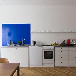 Ejemplo de cocina lineal, contemporánea, grande, abierta, sin isla, con fregadero encastrado, armarios con paneles lisos, puertas de armario blancas, encimera de acero inoxidable, salpicadero azul, salpicadero de piedra caliza, electrodomésticos blancos, suelo de madera oscura y suelo marrón