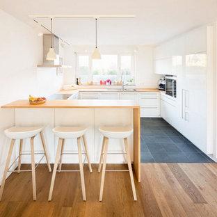 Ejemplo de cocina en U, escandinava, grande, abierta, con armarios con paneles lisos, puertas de armario blancas, encimera de madera, electrodomésticos con paneles, suelo de pizarra, península y fregadero encastrado