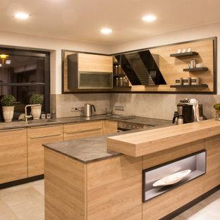 ハンブルクの大きいコンテンポラリースタイルのおしゃれなキッチン (ドロップインシンク、フラットパネル扉のキャビネット、淡色木目調キャビネット、ラミネートカウンター、グレーのキッチンパネル、セメントタイルのキッチンパネル、パネルと同色の調理設備、セメントタイルの床、ベージュの床、グレーのキッチンカウンター) の写真