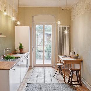Idéer för att renovera ett avskilt, litet shabby chic-inspirerat linjärt kök, med en integrerad diskho, träbänkskiva, grönt stänkskydd, släta luckor, vita skåp och mellanmörkt trägolv