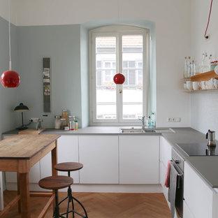 Ispirazione per una piccola cucina a L scandinava chiusa con lavello da incasso, ante lisce, ante bianche, paraspruzzi con piastrelle a mosaico, elettrodomestici in acciaio inossidabile, parquet chiaro, nessuna isola, top in superficie solida e paraspruzzi grigio
