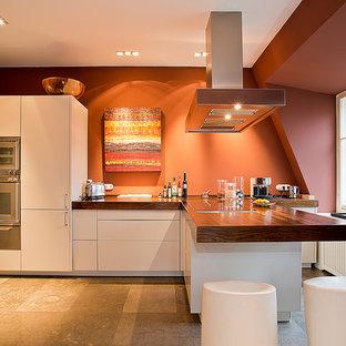 ベルリンの大きいコンテンポラリースタイルのおしゃれなキッチン (フラットパネル扉のキャビネット、白いキャビネット、木材カウンター、赤いキッチンパネル、シルバーの調理設備) の写真