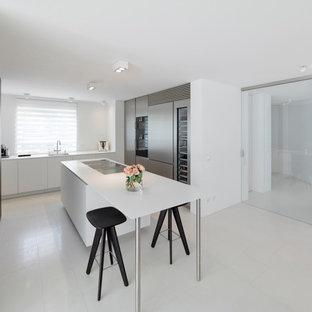Moderne Küche mit Waschbecken, flächenbündigen Schrankfronten, Elektrogeräten mit Frontblende, Kücheninsel, weißem Boden und weißer Arbeitsplatte in Stuttgart