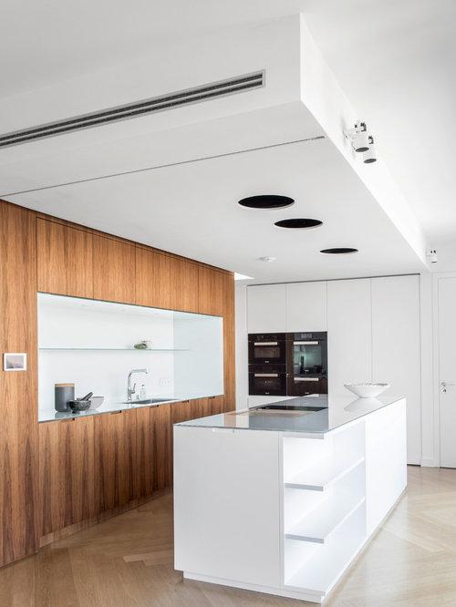Einzeilige moderne küche mit einbauwaschbecken flächenbündigen schrankfronten weißen schränken glas arbeitsplatte