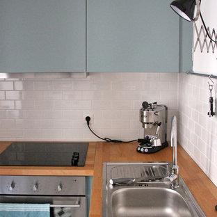 ベルリンのエクレクティックスタイルのおしゃれなキッチン (ドロップインシンク、青いキャビネット、木材カウンター、白いキッチンパネル、シルバーの調理設備の) の写真