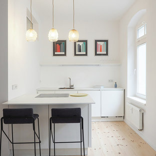 This is an example of a small midcentury u-shaped open plan kitchen in Berlin with a drop-in sink, flat-panel cabinets, white cabinets, light hardwood floors, a peninsula and brown floor.