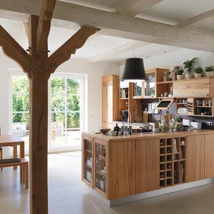 ハノーファーの中サイズのカントリー風おしゃれなキッチン (フラットパネル扉のキャビネット、中間色木目調キャビネット、木材カウンター、黒いキッチンパネル、クッションフロア、ベージュの床) の写真