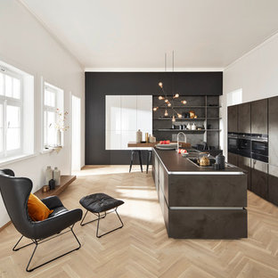 Design ideas for a contemporary galley open plan kitchen in Berlin with a drop-in sink, flat-panel cabinets, grey cabinets, grey splashback, slate splashback, light hardwood floors, with island, brown floor and black appliances.