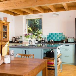 ケルンのシャビーシック調のおしゃれなキッチン (ドロップインシンク、ターコイズのキャビネット、白いキッチンパネル、モザイクタイルのキッチンパネル、無垢フローリング) の写真