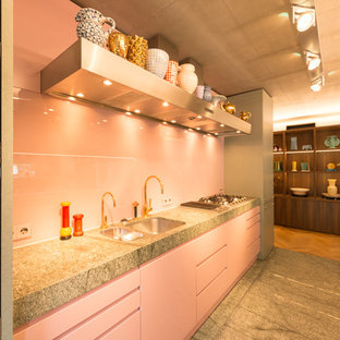 Inspiration for a mid-sized midcentury galley open plan kitchen in Other with a single-bowl sink, flat-panel cabinets, granite benchtops, pink splashback, glass sheet splashback, with island and grey floor.