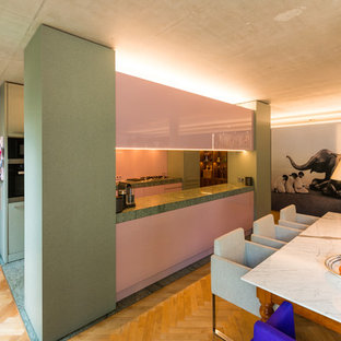 This is an example of a mid-sized midcentury galley open plan kitchen in Other with a single-bowl sink, flat-panel cabinets, granite benchtops, pink splashback, glass sheet splashback, with island and grey floor.