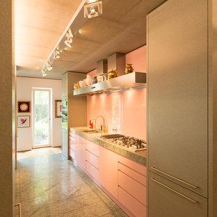 Offene, Zweizeilige, Mittelgroße Retro Küche mit Waschbecken, flächenbündigen Schrankfronten, Granit-Arbeitsplatte, Küchenrückwand in Rosa, Glasrückwand, Kücheninsel und grauem Boden in Sonstige