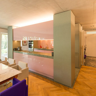 Design ideas for a mid-sized midcentury galley open plan kitchen in Other with a single-bowl sink, flat-panel cabinets, granite benchtops, pink splashback, glass sheet splashback, with island and grey floor.