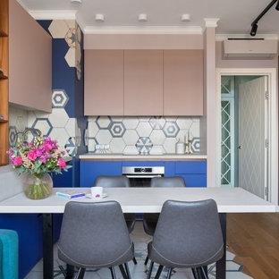 На фото: п-образная кухня в современном стиле с плоскими фасадами, синими фасадами, разноцветным фартуком, техникой из нержавеющей стали, полуостровом, разноцветным полом и белой столешницей