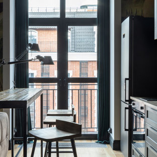 Small industrial single-wall open plan kitchen in Moscow with a drop-in sink, raised-panel cabinets, black cabinets, laminate benchtops, black appliances, light hardwood floors, with island, beige floor and beige benchtop.