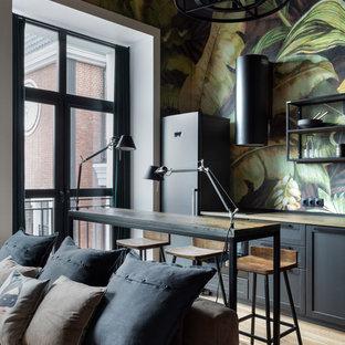 Modelo de cocina industrial, pequeña, abierta, con puertas de armario negras, encimera de madera, salpicadero multicolor, electrodomésticos negros, una isla, suelo beige, encimeras beige, armarios estilo shaker y suelo de madera clara