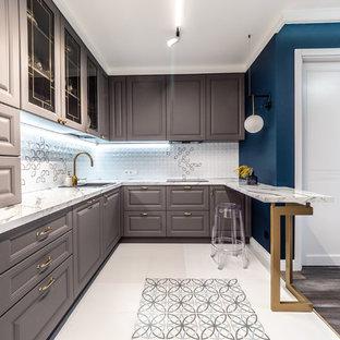 На фото: маленькая п-образная кухня-гостиная в стиле современная классика с серыми фасадами, мраморной столешницей, белым фартуком, фартуком из керамической плитки, техникой под мебельный фасад, полом из керамогранита, полуостровом, белым полом, белой столешницей, накладной раковиной и фасадами с выступающей филенкой