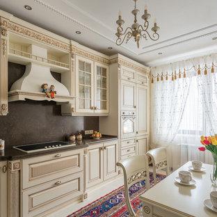 Пример оригинального дизайна: линейная кухня в классическом стиле с обеденным столом, бежевыми фасадами, черным фартуком и фасадами с выступающей филенкой