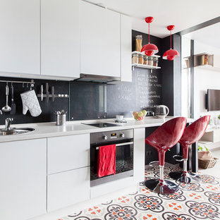 Small scandinavian single-wall open plan kitchen in Moscow with a drop-in sink, flat-panel cabinets, white cabinets, solid surface benchtops, black splashback, glass sheet splashback, stainless steel appliances, grey benchtop, porcelain floors, no island and multi-coloured floor.