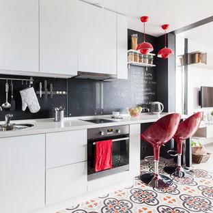 Удачное сочетание для дизайна помещения: маленькая линейная кухня-гостиная в скандинавском стиле с накладной раковиной, плоскими фасадами, белыми фасадами, столешницей из акрилового камня, черным фартуком, фартуком из стекла, техникой из нержавеющей стали, серой столешницей, полом из керамогранита и разноцветным полом без острова - самое интересное для вас