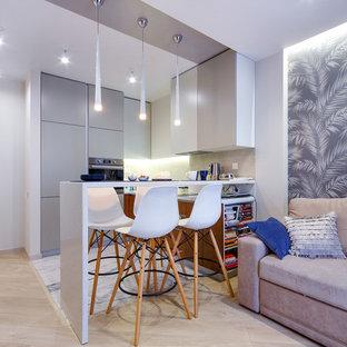 Пример оригинального дизайна интерьера: маленькая п-образная кухня-гостиная в современном стиле с врезной раковиной, плоскими фасадами, столешницей из акрилового камня, техникой из нержавеющей стали, полом из керамогранита, полуостровом, белым полом, белой столешницей, серыми фасадами и серым фартуком