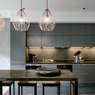 Inspiration for a mid-sized contemporary l-shaped open plan kitchen in Other with grey cabinets, solid surface benchtops, porcelain splashback, porcelain floors, grey floor, grey benchtop, an undermount sink, flat-panel cabinets, grey splashback, black appliances and with island.
