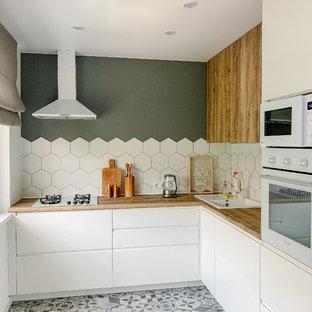 Неиссякаемый источник вдохновения для домашнего уюта: кухня в современном стиле с накладной раковиной, плоскими фасадами, белыми фасадами, белым фартуком, серым полом и коричневой столешницей