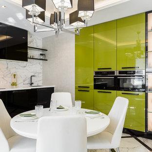 На фото: большая угловая кухня в современном стиле с обеденным столом, врезной раковиной, зелеными фасадами, столешницей из акрилового камня, белым фартуком, фартуком из керамической плитки, черной техникой, полом из керамогранита, белым полом, белой столешницей и плоскими фасадами без острова с