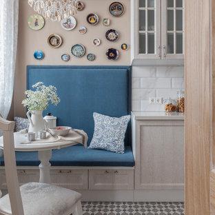 На фото: кухня в стиле современная классика с фасадами с утопленной филенкой, светлыми деревянными фасадами, белым фартуком, серым полом и белой столешницей с