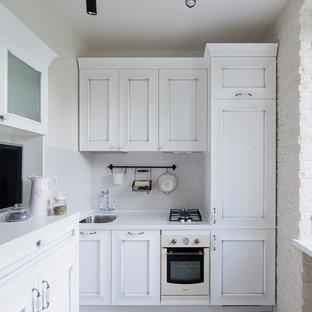 Пример оригинального дизайна: отдельная, линейная кухня в современном стиле с врезной раковиной, фасадами с утопленной филенкой, белыми фасадами, белым фартуком, белой техникой и серым полом без острова