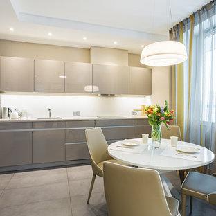 Стильный дизайн: угловая кухня среднего размера в современном стиле с плоскими фасадами, серыми фасадами, белым фартуком, черной техникой, серым полом и белой столешницей без острова - последний тренд