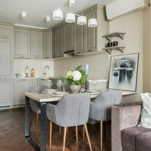 На фото: п-образная кухня-гостиная в стиле неоклассика (современная классика) с фасадами с выступающей филенкой, серыми фасадами, бежевым фартуком, техникой под мебельный фасад, паркетным полом среднего тона, полуостровом и бежевой столешницей