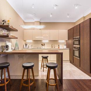 Свежая идея для дизайна: большая угловая кухня в современном стиле с обеденным столом, врезной раковиной, плоскими фасадами, бежевыми фасадами, столешницей из кварцевого агломерата, бежевым фартуком, фартуком из керамической плитки, техникой из нержавеющей стали, полом из керамогранита, бежевым полом, бежевой столешницей и полуостровом - отличное фото интерьера