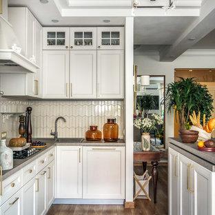 Источник вдохновения для домашнего уюта: угловая кухня среднего размера в стиле неоклассика (современная классика) с бежевыми фасадами, столешницей из ламината, бежевым фартуком, фартуком из удлиненной плитки, полом из ламината, островом, накладной раковиной, фасадами с утопленной филенкой, коричневым полом и серой столешницей