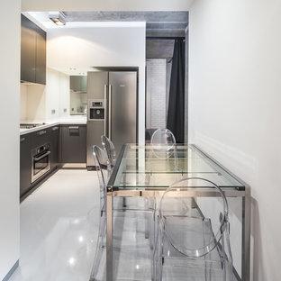 Пример оригинального дизайна интерьера: маленькая угловая кухня в современном стиле с обеденным столом, плоскими фасадами, серыми фасадами, техникой из нержавеющей стали, бетонным полом, серым полом, белой столешницей и белым фартуком