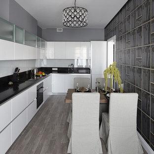 Пример оригинального дизайна: угловая кухня среднего размера в современном стиле с обеденным столом, плоскими фасадами, белыми фасадами, столешницей из кварцевого агломерата, белым фартуком, фартуком из стекла, черной техникой, черной столешницей и серым полом без острова