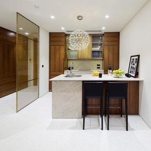 Выдающиеся фото от архитекторов и дизайнеров интерьера: параллельная кухня в современном стиле с врезной раковиной, плоскими фасадами, темными деревянными фасадами, бежевым фартуком, техникой под мебельный фасад и полуостровом