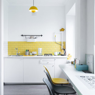 This is an example of a scandinavian single-wall kitchen in Moscow with a single-bowl sink, flat-panel cabinets, white cabinets, yellow splashback, subway tile splashback, dark hardwood floors and no island.