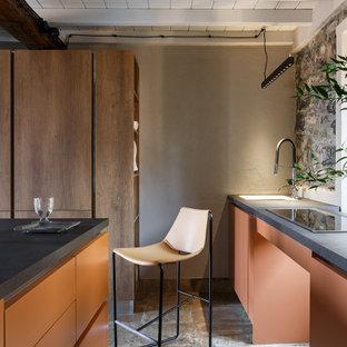 Imagen de cocina de galera, mediterránea, pequeña, con armarios con paneles lisos, encimera de laminado, una isla y encimeras negras