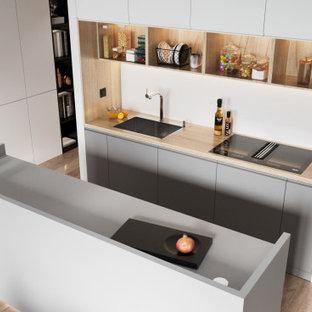 バレンシアの中くらいのコンテンポラリースタイルのおしゃれなキッチン (アンダーカウンターシンク、フラットパネル扉のキャビネット、グレーのキャビネット、木材カウンター、白いキッチンパネル、黒い調理設備、クッションフロア、ベージュの床、ベージュのキッチンカウンター) の写真