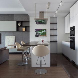 Идея дизайна: кухня-гостиная в современном стиле с плоскими фасадами, белыми фасадами, черной техникой, полуостровом, коричневым полом и барной стойкой