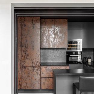 На фото: п-образная кухня среднего размера в современном стиле с плоскими фасадами, столешницей из кварцевого агломерата, черным фартуком, черной техникой, бетонным полом, серым полом, искусственно-состаренными фасадами, полуостровом и черной столешницей