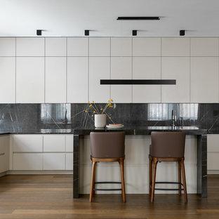 Пример оригинального дизайна: п-образная кухня-гостиная в современном стиле с плоскими фасадами, белыми фасадами, мраморной столешницей, черным фартуком, фартуком из мрамора, техникой из нержавеющей стали, паркетным полом среднего тона, островом, коричневым полом и черной столешницей