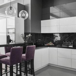 Стильный дизайн: угловая кухня-гостиная в современном стиле с плоскими фасадами, белыми фасадами, черным фартуком, полуостровом, серым полом и техникой из нержавеющей стали - последний тренд